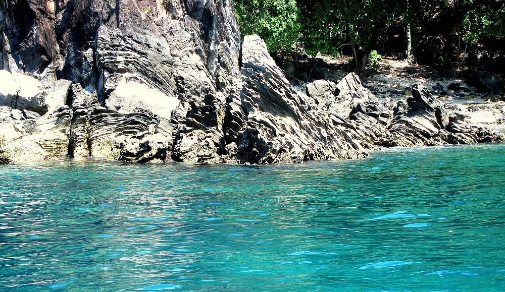 22 Bei Pulisan ragt Lavagestein aus dem türkisfarbenem Meer