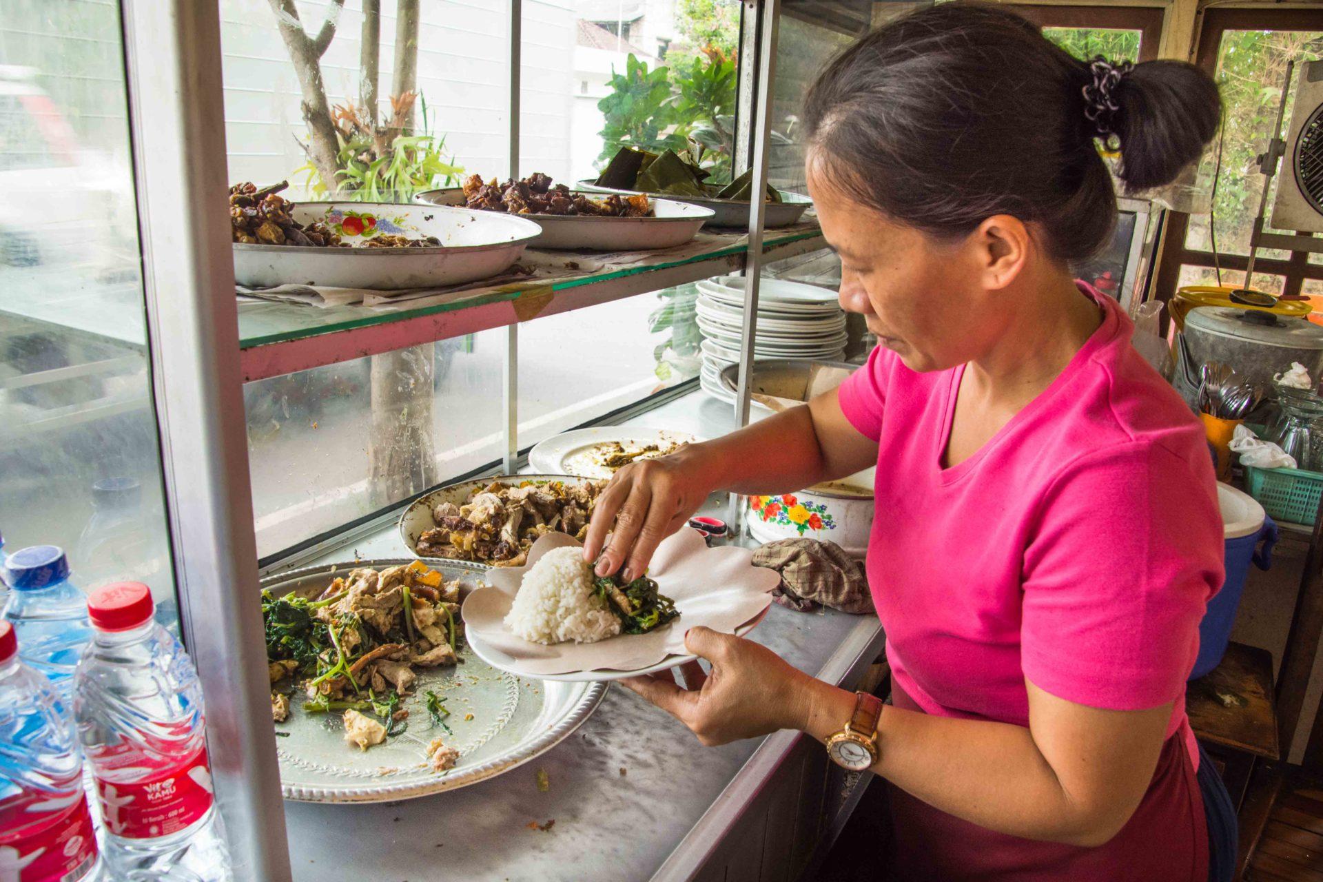 Babi Guling wird mit frischen Zutaten angerichtet